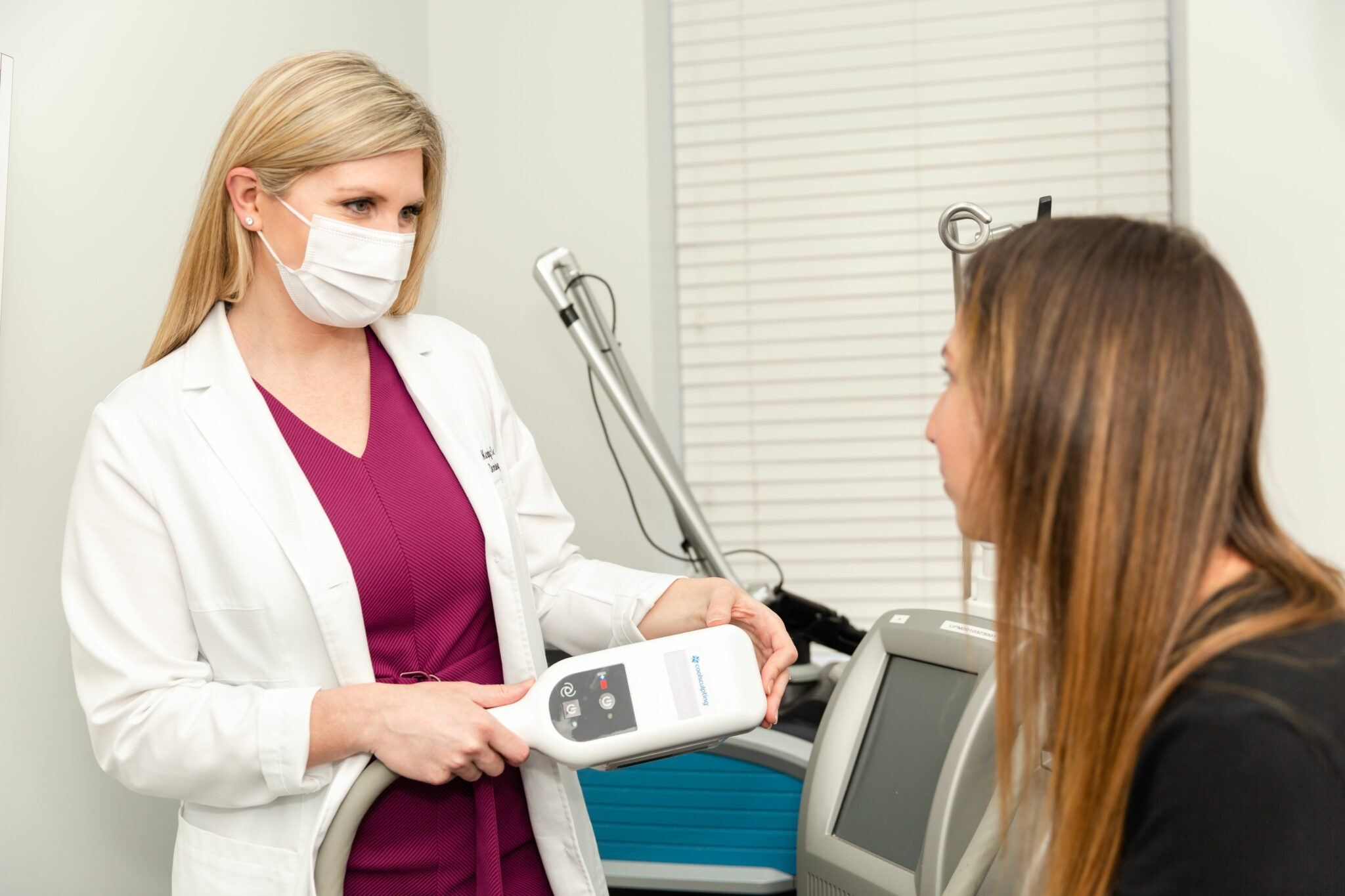 dermatologist explaining to a patient the difference between CoolSculpting and CoolTone for body contouring in NYC, NY