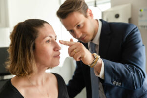 Plastic Surgeon Dr. Wilson is examining his patient's face at Laser & Skin Surgery in NYC, NY.